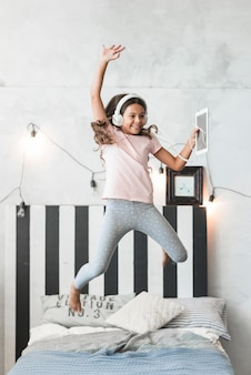 Smiling girl wearing headphone jumping over the bed with digital tablet