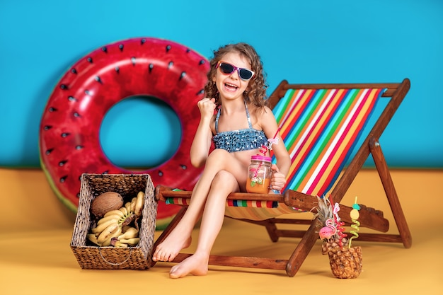 Smiling girl wearing swimsuit and sunglasses holding jar with juice or cocktail with multicolored straws sitting in rainbow deck chair