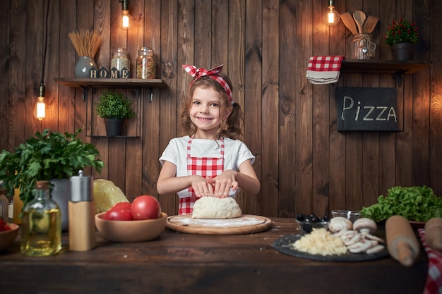 Smiling girl wearing white t-shirt with checkered apron and headband kneading bread dough on table filled with ingredients for pizza in stylish wooden kitchen.
