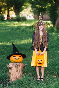 Smiling girl in witch costume near pumpkin