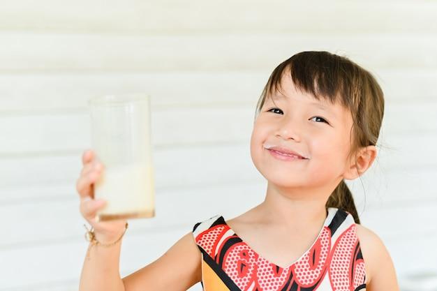 ミルクのガラスを持つ少女の笑顔、牛乳を飲むと口ひげを残して少女