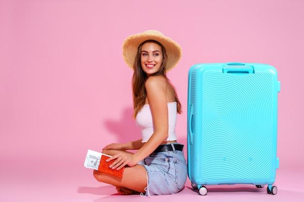Улыбающаяся девушка с билетами отправится в путешествие, сидя возле чемодана в шортах и соломенной шляпе пи ...