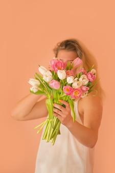 手にブロンドの髪と花のチューリップを持つ笑顔の女の子。春にピンクのチューリップの花束を保持している若い素敵な女の子