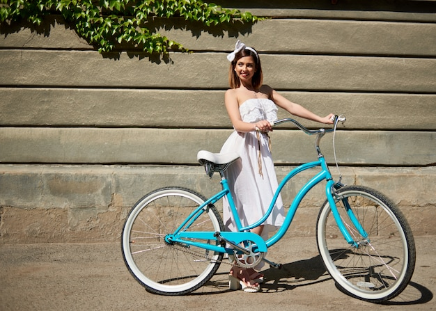 Smiling girl with a blue vintage bicycle looking away on a wall background with green creeper at sunny day