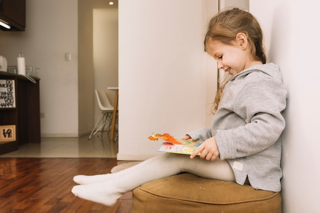 Smiling girl with book sitting on floor