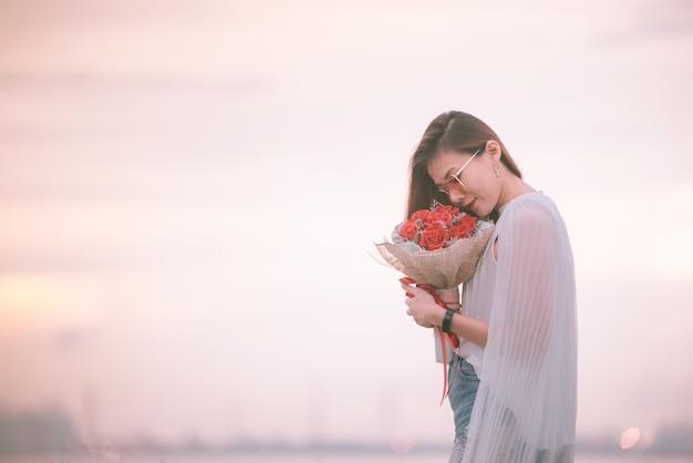 Улыбающаяся девушка с букетом красных роз, портрет довольной молодой женщины