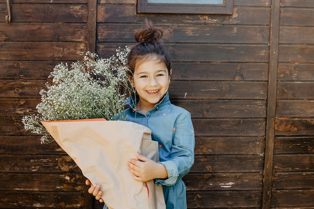 Smiling girl with bouquet of wild flowers