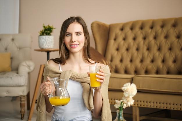 Улыбающаяся девушка с подтяжками держит в руках стакан и кувшин с соком