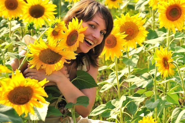 Улыбающаяся девушка с каштановыми волосами в цветочном поле держит подсолнух в руке и смотрит