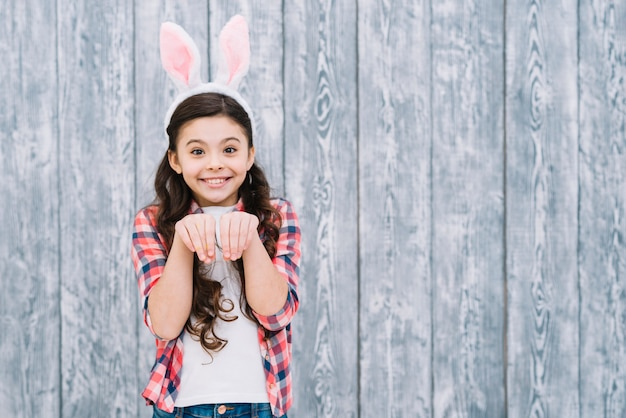 Smiling girl with bunny ears posing like rabbit against gray wooden desk