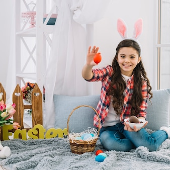 Smiling girl with bunny ears sitting on bed showing red egg on easter day