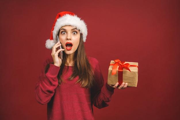 電話で呼び出してクリスマスプレゼントとゴールディングギフトを持つ少女の笑顔