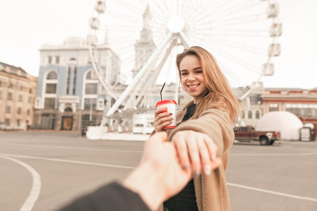 Smiling girl with a cup of coffee holds her husband's hand and looks at the camera at the background of the ferris wheel