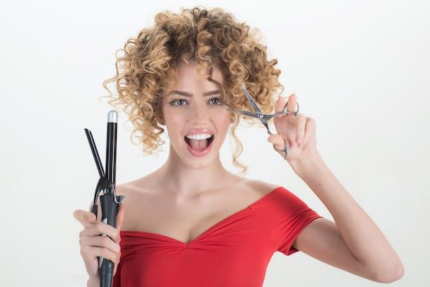 Улыбающаяся девушка с вьющимися волосами держит парикмахерское оборудование, ножницы, индустрия красоты