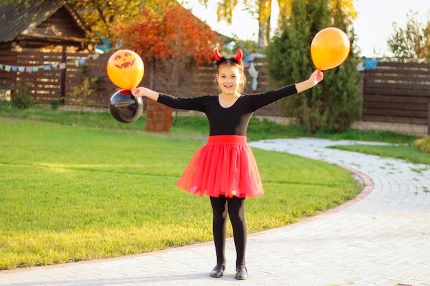 Улыбающаяся девочка с темными волосами в костюме хэллоуина, держащая оранжевые и черные воздушные шары на открытом воздухе, весело встречает хэллоуин.