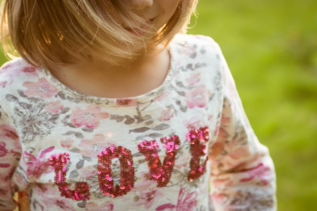 Smiling girl with developing hair in a t-shirt with the inscription love.
