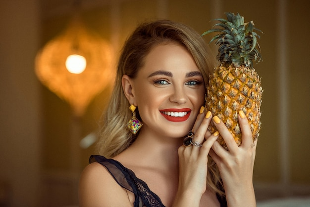 Smiling girl with evening make up wearing accessories posing and holding pineapple, close up.