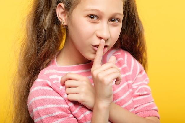 唇に指で笑顔の女の子。いたずらっ子の秘密と陰謀。