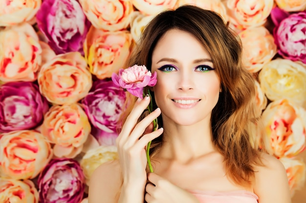 Smiling girl with flower on blossom flowers. woman fashion model with coloring hairstyle, manicure and makeup