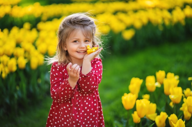Smiling girl with a flower in her hands