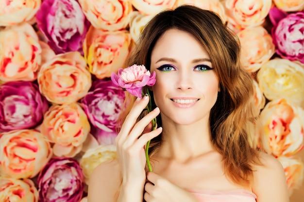 花の花に花と笑顔の女の子。ヘアスタイル、マニキュア、メイクを着色する女性のファッションモデル