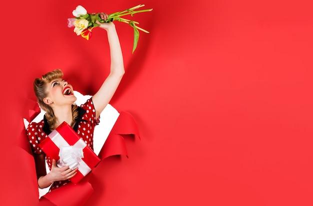 Улыбающаяся девочка с цветами и подарком. женщина с тюльпанами и настоящий момент, глядя через отверстие. скопируйте место для рекламы.