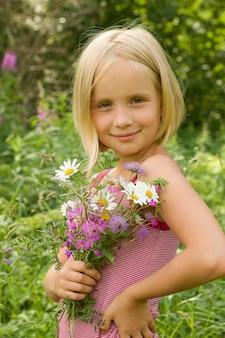 Улыбающаяся девочка с цветами на открытом воздухе
