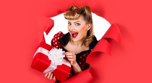 Улыбающаяся девочка с подарком, глядя через отверстие в бумаге. разрыв бумаги. счастливая женщина с ретро прической с настоящим моментом. скопируйте место для рекламы.