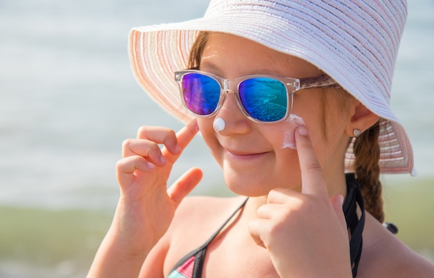 Smiling girl with hat smears protective face cream on the beach