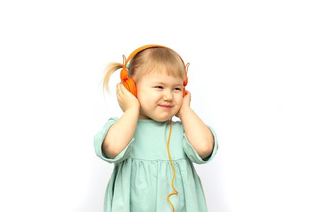 白い背景で隔離の音楽を聴くヘッドフォンで笑顔の女の子