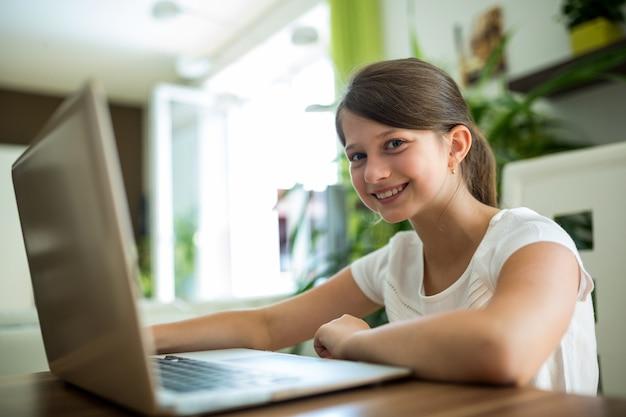 Улыбающаяся девушка с ноутбуком в гостиной