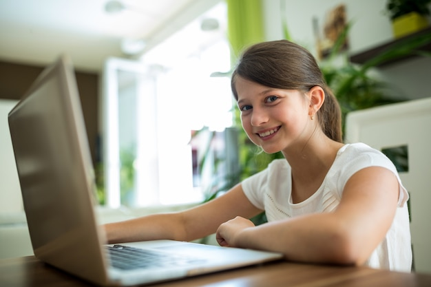Smiling girl with laptop in the living room