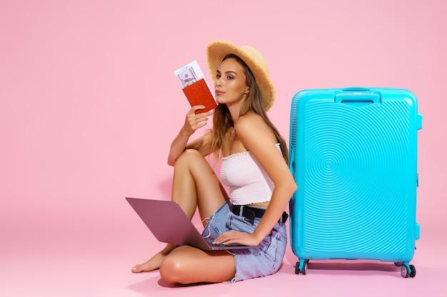 Улыбающаяся девушка с деньгами и паспортом на ноутбуке отправится в путешествие, сидя возле чемодана в ш ...