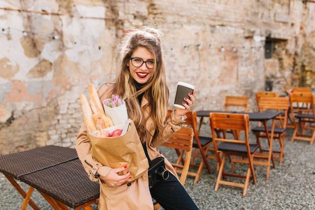 Улыбающаяся девушка с длинными вьющимися волосами держит сумку с едой с рынка и застенчиво позирует. милая молодая женщина устало прислонилась к забору после покупок. покупка продуктов, покупка еды