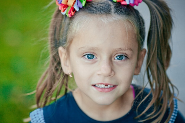 Smiling girl with missing tooth in summertime