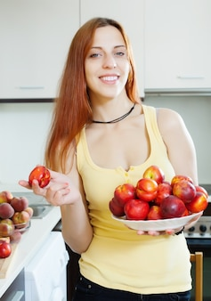 Smiling girl with nectarines