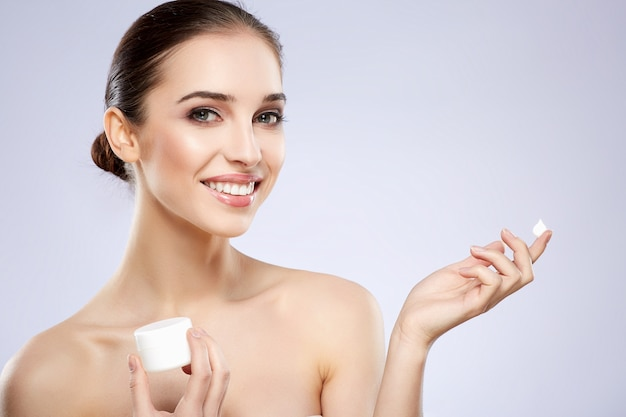 Smiling girl with nude make up posing at grey studio background, beauty photo concept, perfect skin, holding product, portrait.