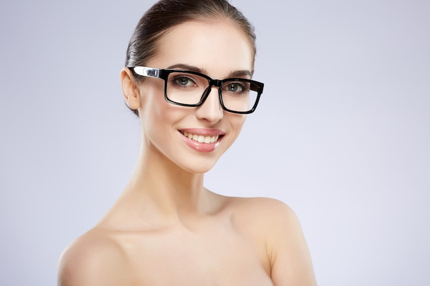Smiling girl with nude make up posing at grey studio background, beauty photo concept, perfect skin, wearing glasses, vision concept, looking at camera.