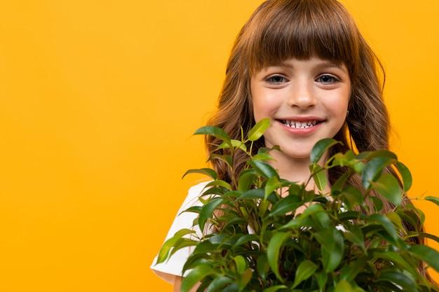 Улыбающаяся девушка с растением на оранжевом фоне крупным планом