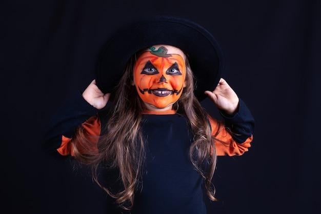Улыбающаяся девочка с макияжем из тыквы на лице, держащая черную шляпу на черной стене, смешное празднование хэллоуина.