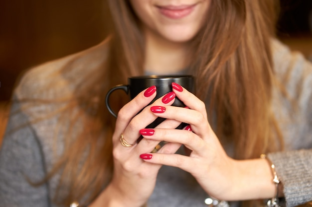Smiling girl with red nails holding a cup of coffee.