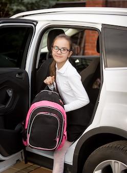 Улыбающаяся девочка со школьной сумкой выходит из машины