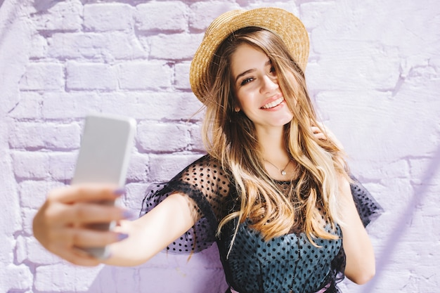 Smiling girl with shiny hair enjoying good weather during walk and making selfie