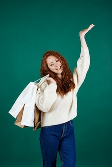 스튜디오 촬영에서 쇼핑 봉투와 함께 웃는 소녀
