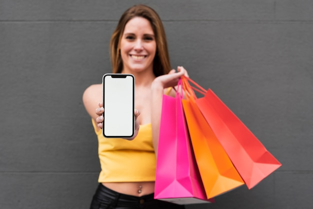 Smiling girl with shopping bags holding phone
