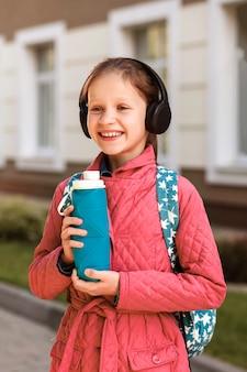 街の背景に彼女の手に水のシリコーンボトルと笑顔の女の子