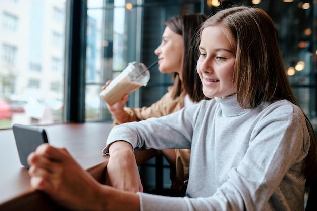 スマートフォンのカフェのテーブルに座っているとカクテルを持っている彼女の母親と一緒にビデオを見ていると笑顔の女の子