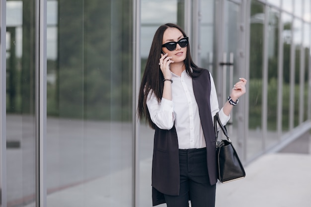 Smiling girl with sunglasses talking on her phone