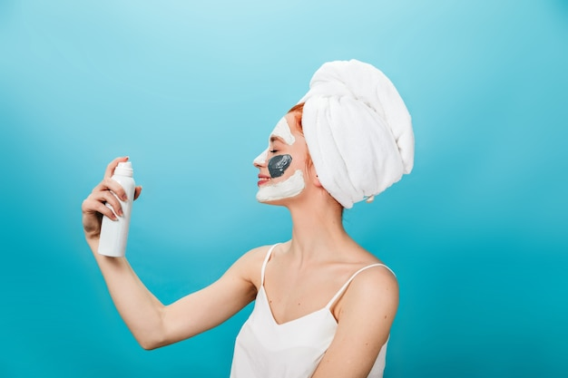 化粧品ボトルを保持している頭にタオルで笑顔の女の子。青い背景の上に立っているフェイスマスクと笑う女性のスタジオショット。
