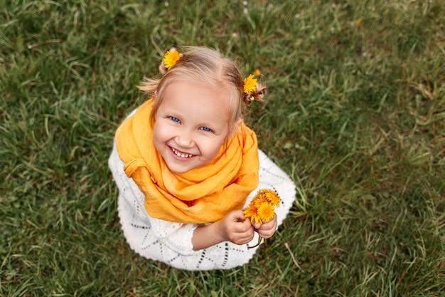그녀의 손에 노란 꽃을 들고 웃는 소녀 머리에 노란 민들레